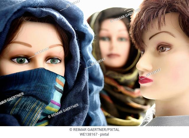 Two mannequin heads in hijabs and one without