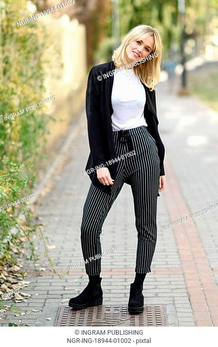 Pretty blonde woman smiling in urban background. Young girl wearing black blazer jacket and striped trousers standing in the street