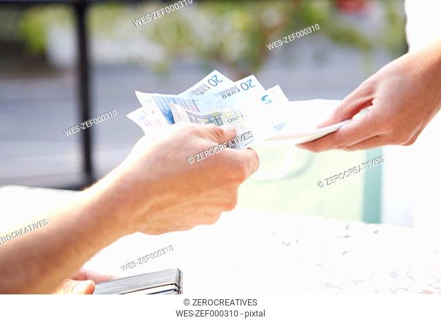 Man paying with Euro notes in a pavement cafe