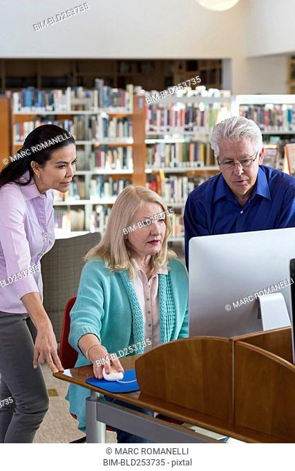 Older people using computer in library