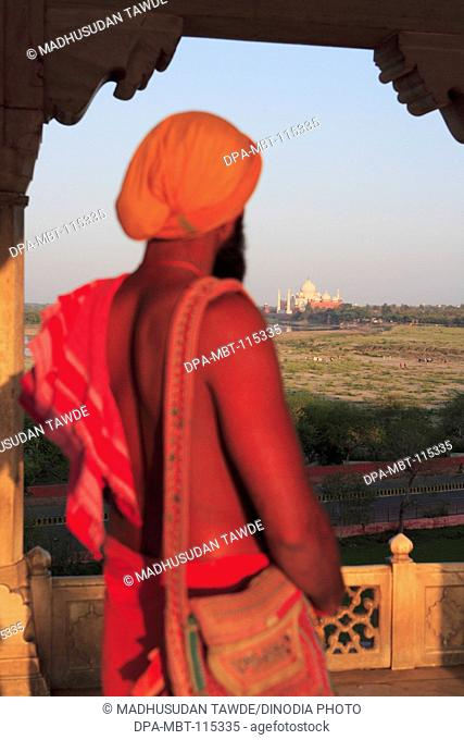 Sadhu watching Taj Mahal view from Agra fort built in 16th Century by Mughal emperor on west bank of the Yamuna River , Agra , Uttar Pradesh