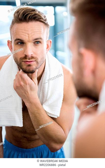 Handsome man looking in mirror