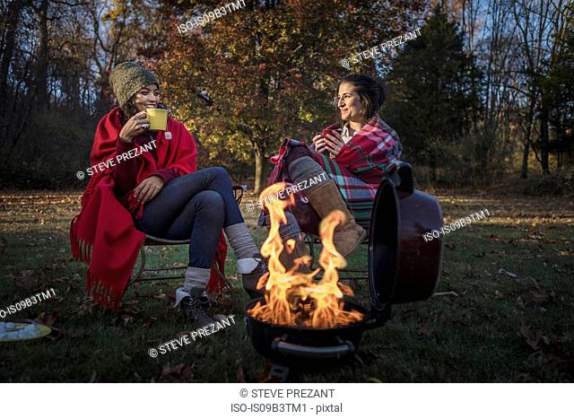 Two female friends wrapped in blankets by campfire