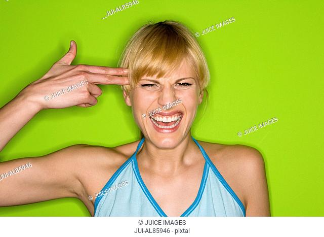 Woman mimicking gun with hand pointed at head