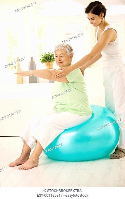 Senior woman doing fit ball exercise