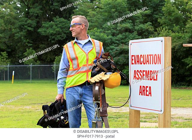 Communications engineer with climbing equipment and tool belts at evacuation assembly area