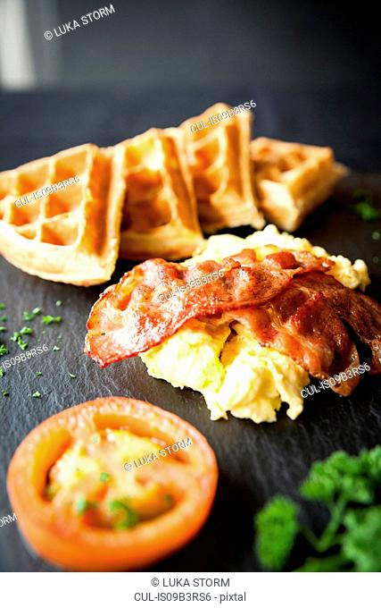 Waffles with bacon, omelette and tomato breakfast on slate