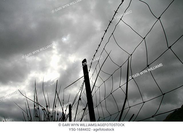 metal wire fence barrier and dark cloudy moody sky in field in countryside