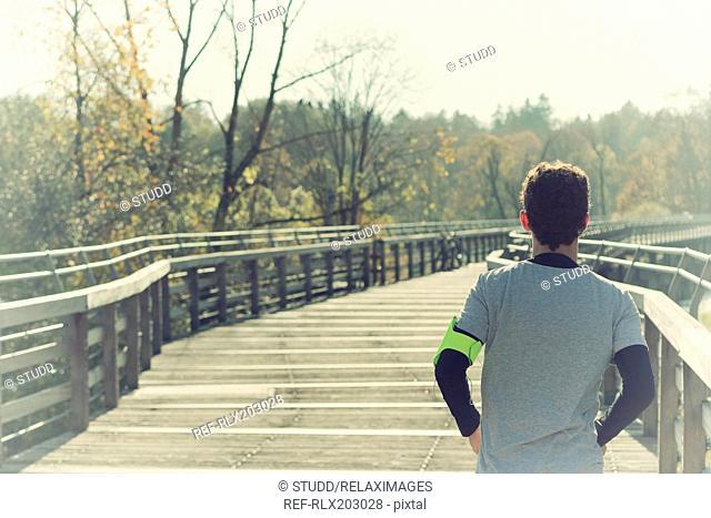 Young man jogging smartphone armband winter bridge