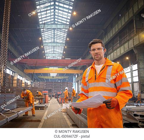 Engineer holding plans in marine fabrication factory, portrait
