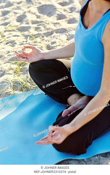Pregnant woman practicing yoga at beach