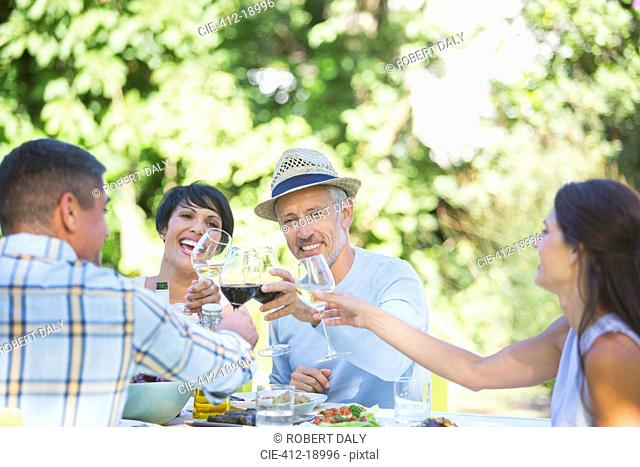 Friends toasting each other at table outdoors