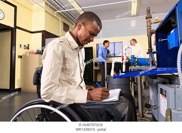 Student in wheelchair studying furnace electronic control system in HVAC classroom