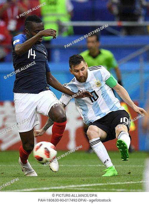 30 June 2018, Russia, Kazan: Football World Cup, France vs Argentina at the Kazan Arena. Lionel Messi (r) of Argentina and Blaise Matuidi of Frankreich vie for...