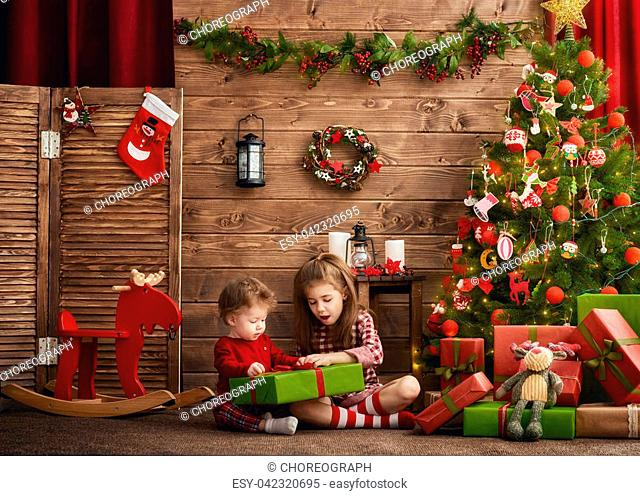 Merry Christmas and Happy Holidays! Two cheerful cute children girls with present. Kids hold a gift box near Christmas tree indoors