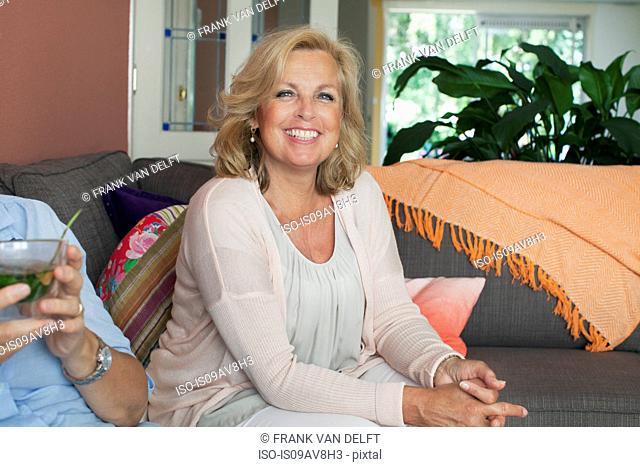 Portrait of mature woman sitting on sofa, smiling