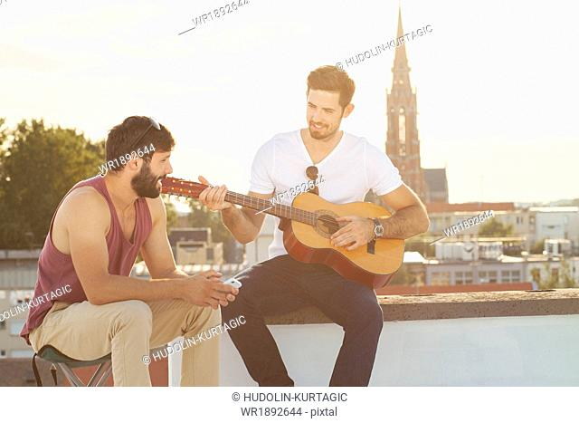 Young man with friend playing guitar at rooftop party