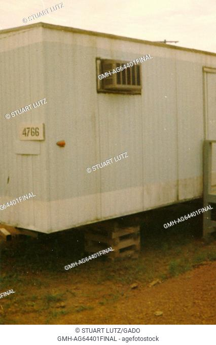 An exterior photograph of a plain, white trailer on a military base, an air conditioning unit can be seen, Long Binh, Vietnam, 1964