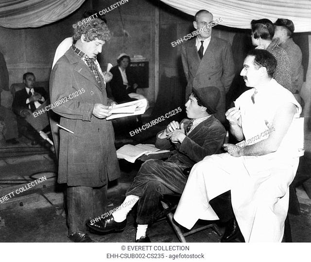 Harpo, Chico and Groucho Marx on the set of MGM's movie, A DAY AT THE RACES. Oct. 8, 1937. Director Sam Wood standing in right background