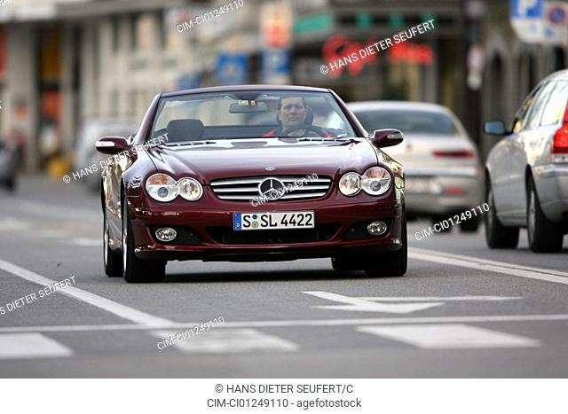 Mercedes SL 500, ruby colored, model year 2006-, driving, diagonal from the front, frontal view, City, open top