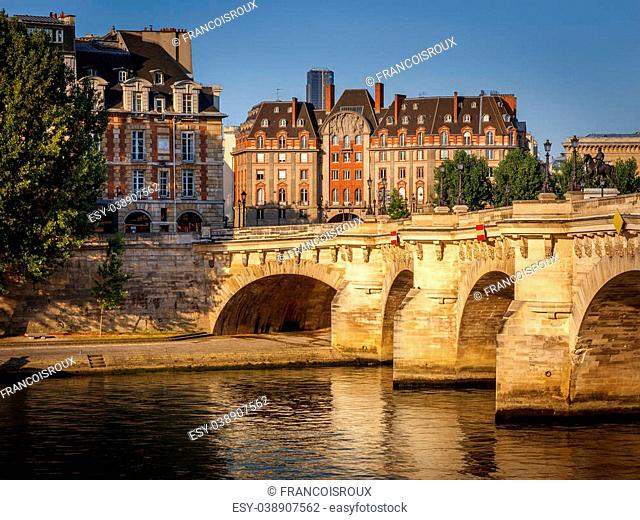 Paris at dawn. Pont Neuf across the River Seine and the buildings on the west end of Ile de la Cité are slowly waking to morning's warm sunrays