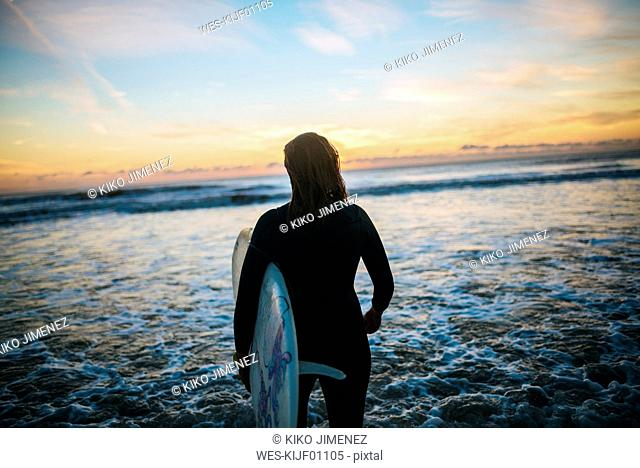 Back view of young woman with surfboard standing at seashore watching sunset