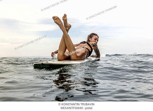 Indonesia, Java, woman lying on surfboard on the sea