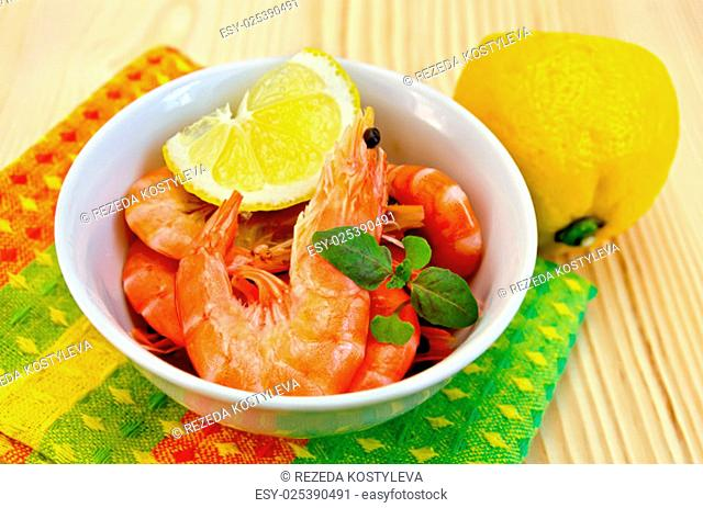 Raw shrimp in a white bowl with lemon, basil and a napkin on a wooden board