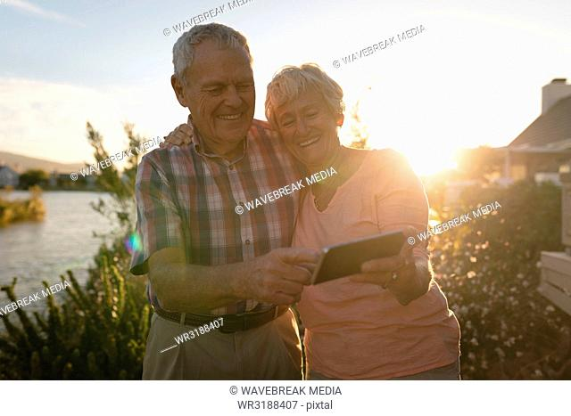 Senior couple using mobile phone in the backyard