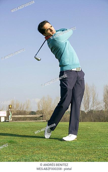 Golfer hitting a golf ball in a golf course