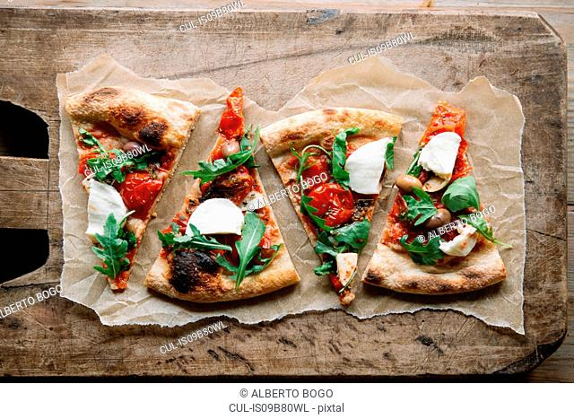 Pizza slices on chopping board, overhead view