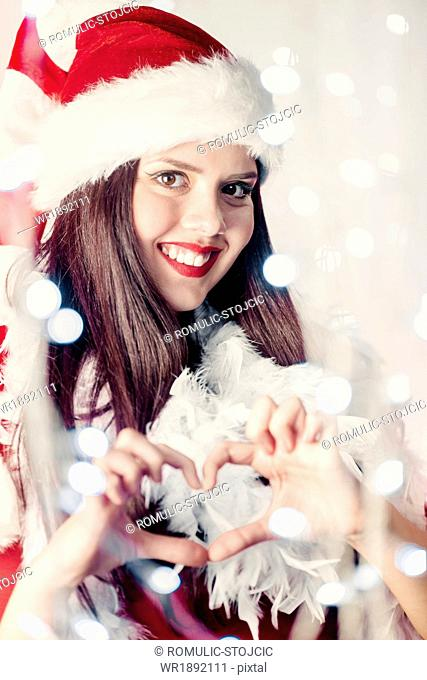 Young woman in Santa Claus costume making heart shape with hands