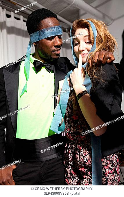 Couple at party, man with streamer covering eyes