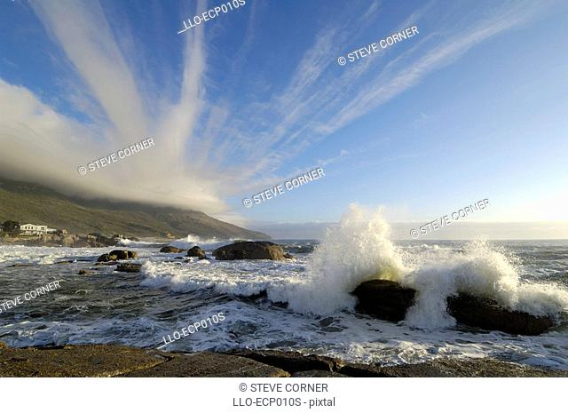 Strange Cloud Formations Emanate from the Table Cloth on the Twelve Apostles over the Bakoven Shoreline  Cape Town, Western Cape Province, South Africa