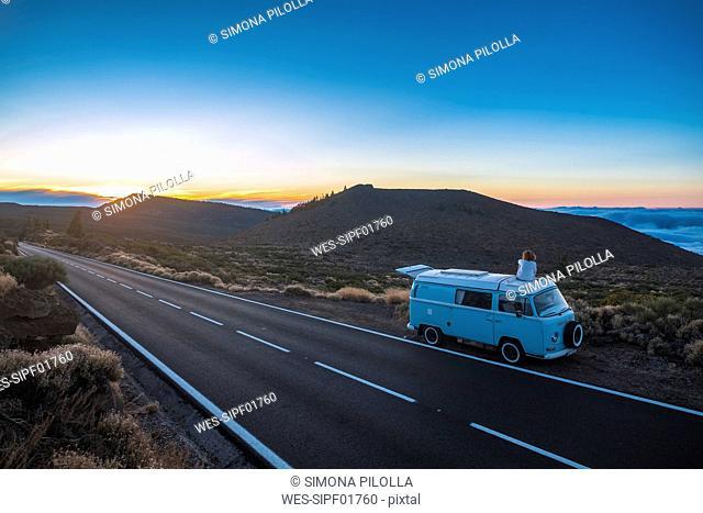 Spain, Tenerife, back view of woman sitting on car roof of van parked at roadside
