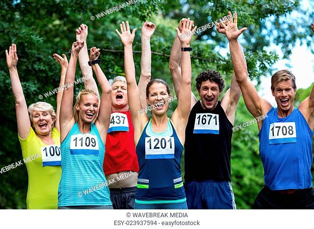 Marathon athletes posing with raised arms