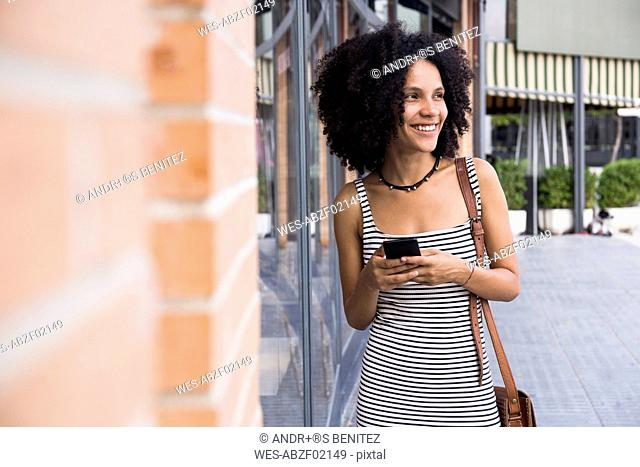 Portrait of smiling young woman with smartphone besides shop window