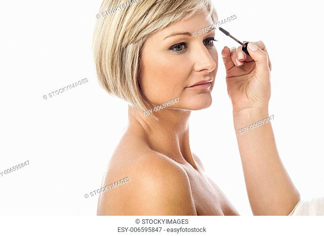 Lady getting makeup applied on her eyebrows