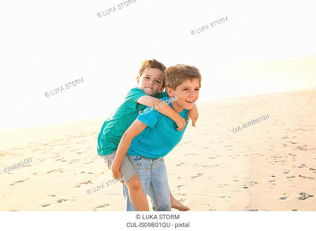 Boy giving brother piggyback on beach