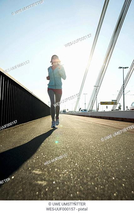 Young female jogger on the move on a bridge