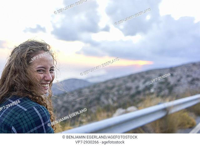 happy young girl during morning sunrise during travel adventure, near Heraklion, Crete, Greece