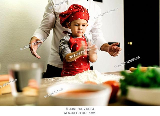 Father and son preparing pizza together