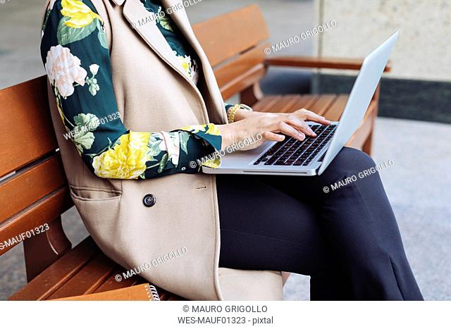 Businesswoman sitting on bench using laptop, partial view