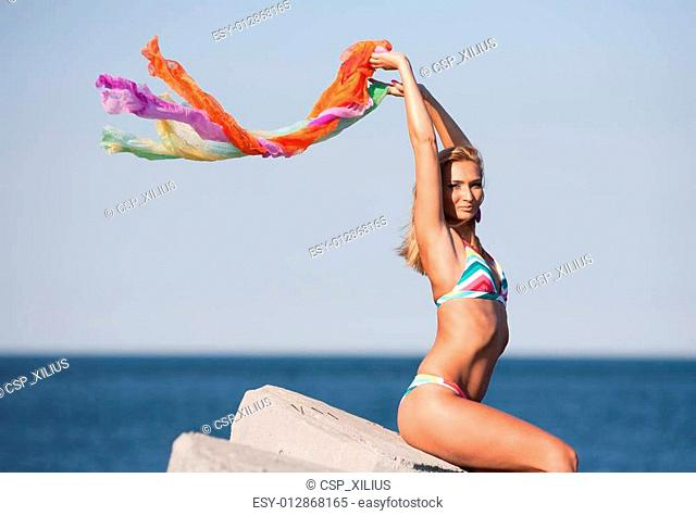 Beautiful young lady with colorful scarf on the beach