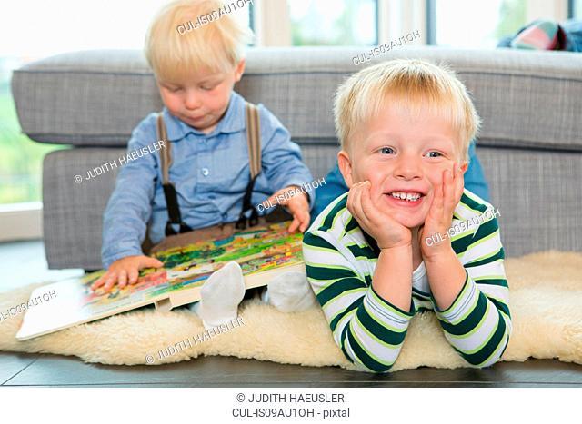 Male toddler reading childrens book on living room floor