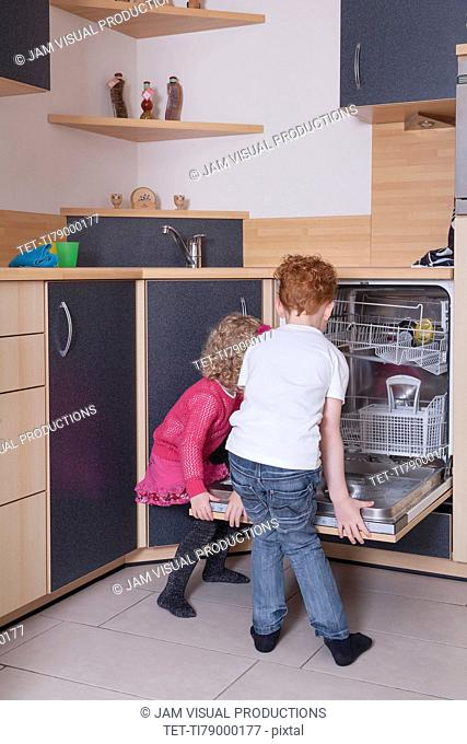 Girl (4-5) and boy (8-9) loading dishwasher