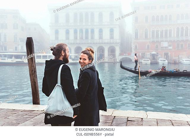 Rear view of couple on misty canal waterfront, Venice, Italy