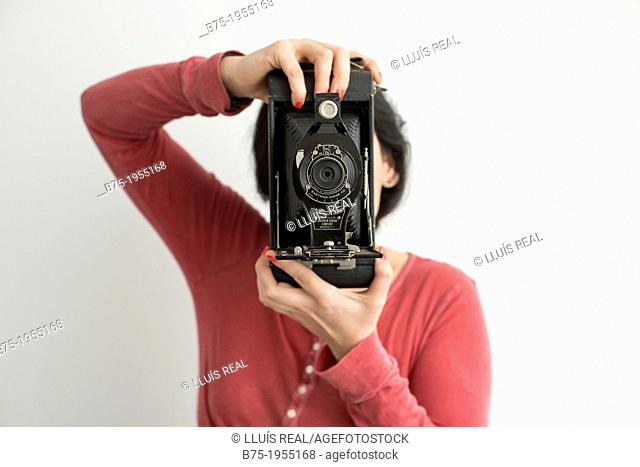 Young woman with face covered with a old photographic camera