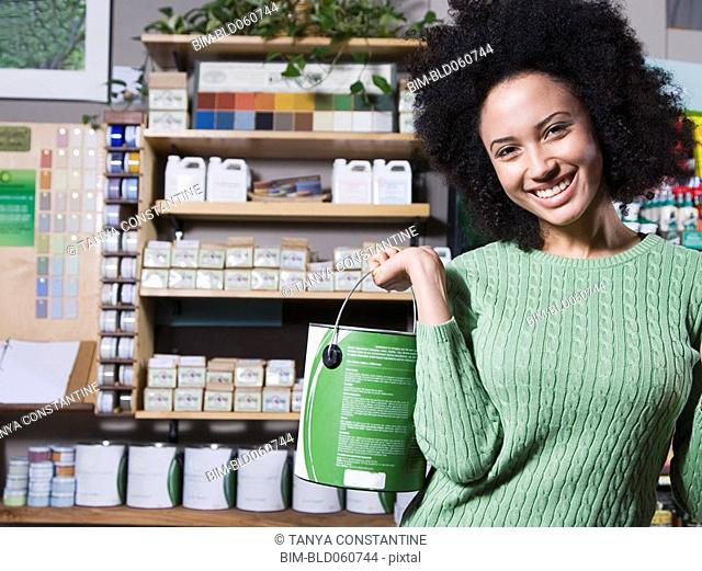 African woman holding paint can in store