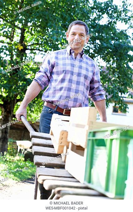 Germany, Saxony, Mature man pushing cart, smiling, portrait
